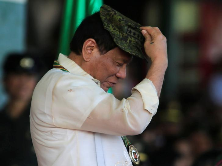 Philippine President Rodrigo Duterte tries on a military hat given to him during the 120th founding anniversary of the Philippine Army (PA) at Taguig city, metro Manila, Philippines April 4, 2017. REUTERS/Romeo Ranoco