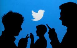 People holding phones are silhouetted against a backdrop projected with the Twitter logo in this illustration picture. REUTERS/Kacper Pempel/Illustration