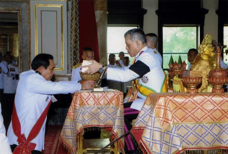 Thailand's King Maha Vajiralongkorn Bodindradebayavarangkun (R) returns the constitution after signing it to Thailand's Prime Minister Prayut Chan-o-cha at Ananta Samakhom Throne Hall in Bangkok, Thailand April 6, 2017. Thailand Royal Household Bureau/Handout via REUTERS