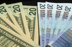 Банкноты доллара США и евро. Париж, 28 октября 2014 года. Доллар подешевел к японской иене в пятницу после того, как США выпустили крылатые ракеты, нанеся удар по авиабазе в Сирии и спровоцировав беспокойство о резкой эскалации сирийского конфликта. REUTERS/Philippe Wojazer