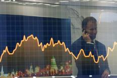 """A participant is reflected in a display showing business and financial information at the VTB Capital """"Russia Calling!"""" Investment Forum in Moscow, Russia, October 2, 2014. REUTERS/Maxim Shemetov/File Photo"""