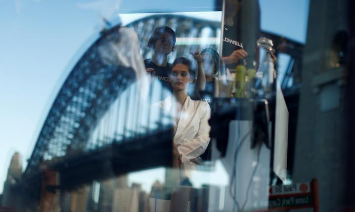 The Sydney Harbour Bridge is reflected in the window of a hair salon as a model gets her hair styled before the Manning Cartell catwalk show at Australian Fashion Week May 17, 2016.   REUTERS/Jason Reed/File Photo