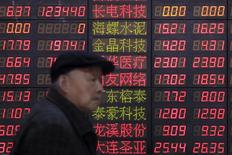 An investor walks past an electronic board showing stock information at a brokerage house in Shanghai, China, March 14, 2016. REUTERS/Aly Song