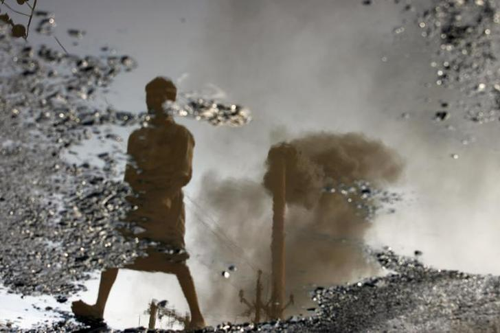 A chimney is reflected in a puddle polluted with chemicals at an industrial area of Surat November 25, 2009. REUTERS/Arko Datta/Files