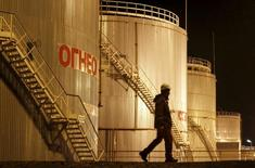 A worker walks past oil tanks of Oil&Gas-Processing Plant on oil fields operated by a subsidiary of the KazMunayGas Exploration Production JSC in Kyzylorda region, southern Kazakhstan, January 21, 2016. Picture taken January 21, 2016. REUTERS/Shamil Zhumatov