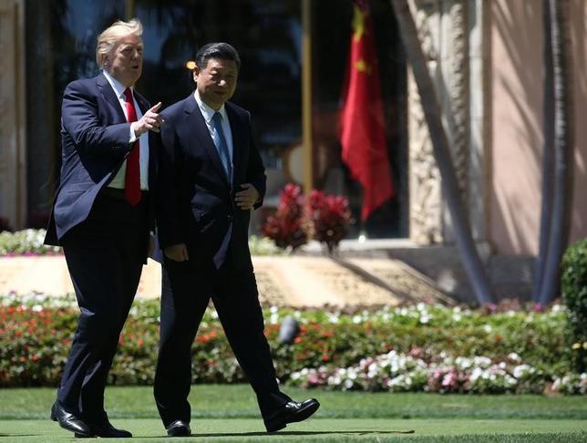 4月7日、トランプ米大統領は前日から2日間の日程で始まった中国の習近平国家主席との首脳会談で進展が見られ、米中両国は多くの問題を乗り越えられるとの認識を示した。写真は同日、習主席と並んで歩くトランプ氏(2017年 ロイター/Carlos Barria)