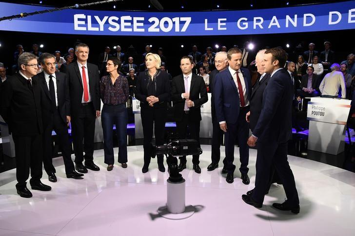 Candidates pose prior to a prime-time televised debate for the French 2017 presidential election in La Plaine Saint-Denis, near Paris, France, April 4, 2017. L to R: Jean-Luc Melenchon of the Parti de Gauche, Francois Fillon of the Republicans party, Jean Lassalle, Nathalie Arthaud of France's extreme-left Lutte Ouvriere party (LO), Marine Le Pen of French National Front (FN), Benoit Hamon of the French Socialist party, Jacques Cheminade, Nicolas Dupont-Aignan of Debout La France group, Francois Asselineau of UPR party, and Emmanuel Macron of the political movement En Marche ! (Onwards !). REUTERS/Lionel Bonaventure/Pool