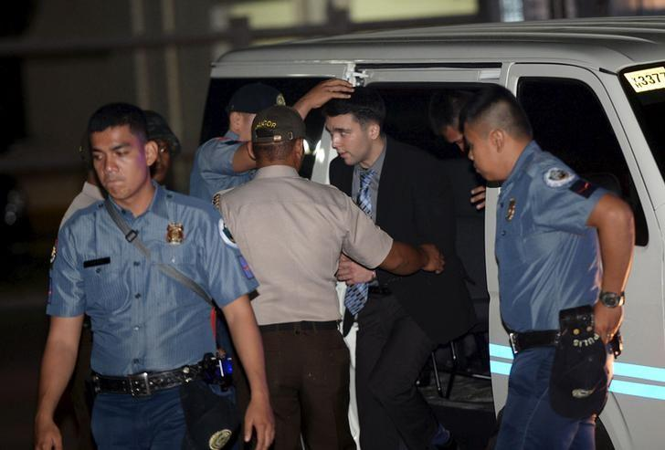 Philippine Bureau of Corrections personnel escort U.S. Marine Lance Corporal Joseph Scott Pemberton (2nd R), after he was found guilty by trial court of killing Jennifer Laude, a transgender woman, upon arrival in a detention facility at Camp Aguinaldo in Quezon city, Metro Manila, December 1, 2015. REUTERS/Ted Aljibe/Pool/Files