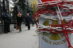 A chain is seen wrapped around a road sign for parking, with the coat of arms of the Central Bank seen on it, near the headquarters of the bank in central Moscow, October 1, 2014. The Russian rouble weakened on Wednesday after the Central Bank conducted its first overnight rouble-dollar swap operation to boost banking liquidity. REUTERS/Sergei Karpukhin (RUSSIA - Tags: BUSINESS)