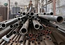 A worker stacks steel pipes in the western Indian city of Ahmedabad November 4, 2014. India's steel consumption is expected to grow at its fastest pace in five years next year on Prime Minister Narendra Modi's infrastructure push, but a scarcity of raw materials means it will be at the expense of another key goal - curbing imports. Picture taken November 4, 2014.      To match INDIA-STEEL/CHINA       REUTERS/Amit Dave (INDIA - Tags: BUSINESS POLITICS COMMODITIES)