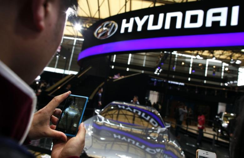 A man takes pictures of a Hyundai car during the 15th Shanghai International Automobile Industry Exhibition in Shanghai April 21, 2013. REUTERS/Carlos Barria/File Photo