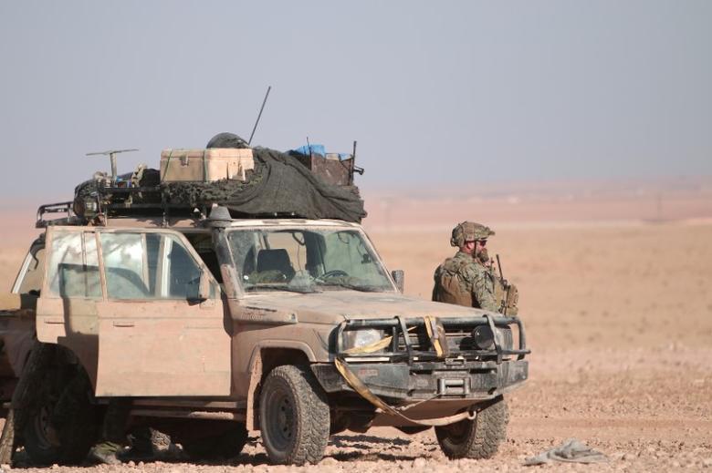 FILE PHOTO: A U.S. fighter stands near a military vehicle, north of Raqqa city, Syria November 6, 2016. REUTERS/Rodi Said