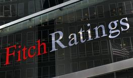 A flag is reflected on the window of the Fitch Ratings headquarters in New York February 6, 2013. REUTERS/Brendan McDermid (UNITED STATES - Tags: BUSINESS)