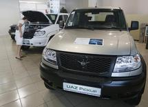 A visitor looks under the bonnet of a car at the KGS Auto Centre dealership selling UAZ all-terrain cars, produced by Russian Sollers UAZ car maker, in Russia's Siberian city of Krasnoyarsk July 10, 2014. Russian car sales plunged 17.3 percent year-on-year in June, according to a lobby group for Europe's top carmakers, accelerating their recent slide and leading the group to slash its forecast for sales in the country this year by 12 percent.   REUTERS/Ilya Naymushin (RUSSIA - Tags: TRANSPORT BUSINESS)