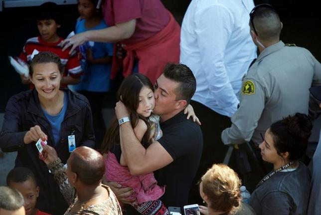 A student who was evacuated after a shooting at North Park Elementary School is embraced after groups of them were reunited with parents waiting at a high school in San Bernardino, California, U.S. April 10, 2017.  REUTERS/Mario Anzuoni/Files