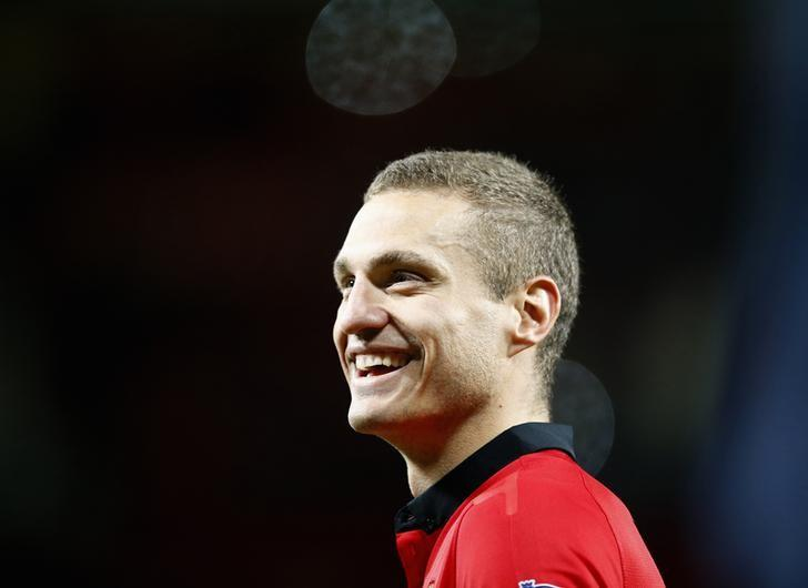 Manchester United's Nemanja Vidic, who has played his final home match for the team, smiles following their English Premier League soccer match against Hull City at Old Trafford in Manchester, northern England May 6, 2014.    REUTERS/Darren Staples/Files