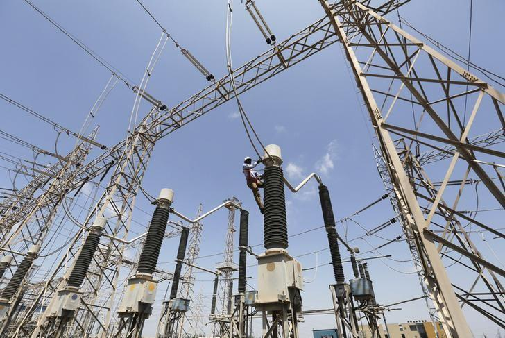 A technician repairs power supply lines at a power plant of Adani Power at Mundra Port in Gujarat April 2, 2014. REUTERS/Amit Dave/Files