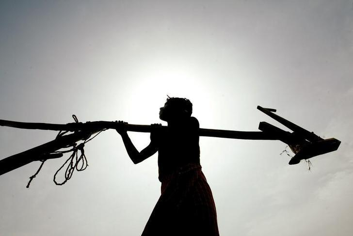A farmer carries his plough under a scorching sun in the village ofPurulia, 300km (186 miles) west of Kolkata, June 6, 2003. REUTERS/JayantaShaw/Files