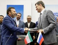 Russian Energy Minister Alexander Novak and Iranian Communications Minister Mahmoud Vaezi exchange documents during a signing ceremony after their meeting in Moscow, Russia, July 29, 2016.  REUTERS/Maxim Zmeyev