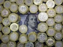 A picture illustration shows Kazakhstan's 100 tenge coins and 100 U.S. dollars banknote in Almaty, Kazakhstan, November 6, 2015. The weighted average of the Kazakh tenge fell to 307.53 per dollar, a fresh all-time closing low, on the Kazakhstan Stock Exchange on Friday from 298.92 in the previous trading session.  REUTERS/Shamil Zhumatov       TPX IMAGES OF THE DAY
