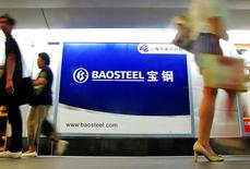 People walk past an advertising board of Baosteel Group in Shanghai, September 9, 2011. REUTERS/China Daily/File Photo  CHINA OUT. NO COMMERCIAL OR EDITORIAL SALES IN CHINA.