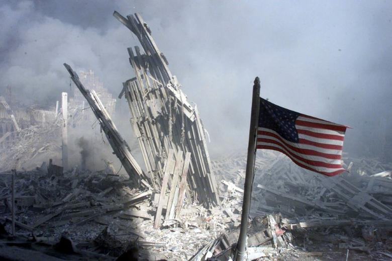 An American flag flies near the base of the destroyed World Trade Center in New York, September 11, 2001. REUTERS/Peter Morgan