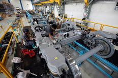 FILE PHOTO: Employees work on the base unit of a metro coach inside India's private railway equipment production unit of Bombardier Transportation at Savli, in the western state of Gujarat, India, May 12, 2010. REUTERS/Amit Dave/File Photo