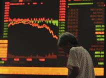 An investor stands in front of an electronic board showing stock information at a brokerage house in Fuyang, Anhui province, July 27, 2015. China stocks plunged more than 8 percent, their biggest one-day drop in more than eight years. REUTERS/Stringer CHINA OUT. NO COMMERCIAL OR EDITORIAL SALES IN CHINA