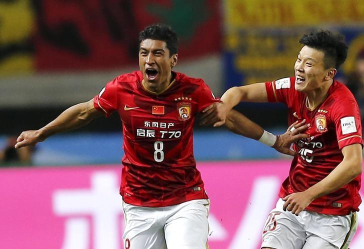 FILE PHOTO - Paulinho (L) of China's Guangzhou Evergrande celebrates with teammate Zou Zheng after scoring against Mexico's Club America during their Club World Cup quarter-final soccer match in Osaka, western Japan, December 13, 2015.  REUTERS/Thomas Peter
