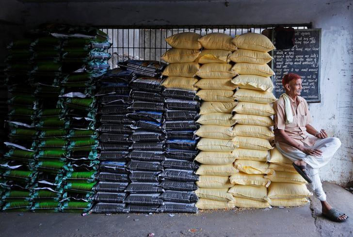 A labourer sits on sacks of food grains while waiting for customers at a wholesale market in Ahmedabad, India, December 14, 2016. REUTERS/Amit Dave/Files