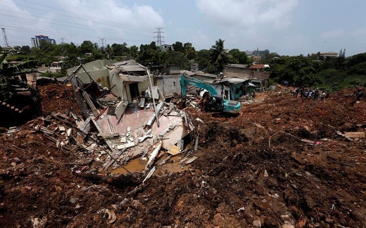 A bako machine works near damaged houses during a rescue mission after a garbage dump collapsed and buried dozens of houses in Colombo, Sri Lanka April 16, 2017. REUTERS/Dinuka Liyanawatte/Files