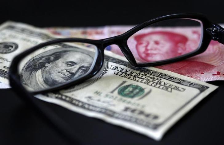 资料图片:2010年10月,置于镜片下的美元和人民币纸币。REUTERS/Nicky Loh