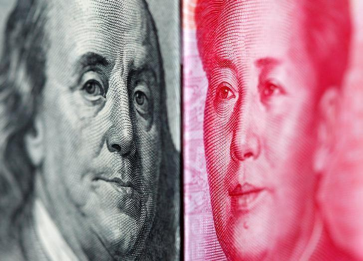 FILE PHOTO: A 100 yuan banknote is placed beside a U.S. 100 dollar banknote in this illustrative photograph taken in Taipei June 20, 2010. REUTERS/Nicky Loh/File Photo