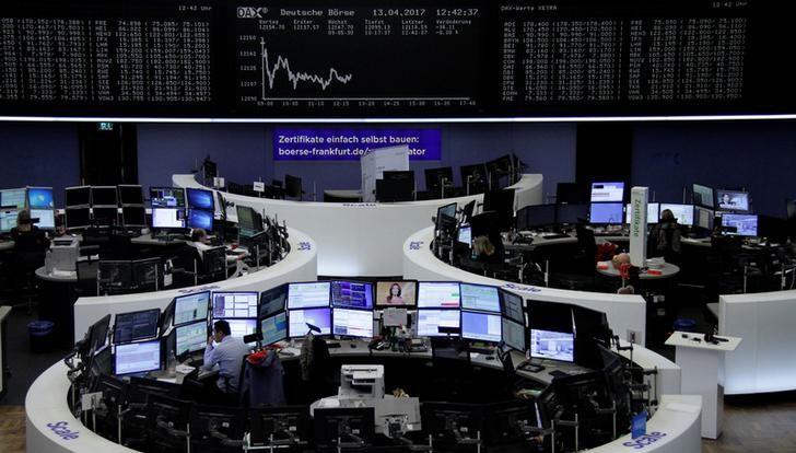 Traders work at their desks in front of the German share price index, DAX board, at the stock exchange in Frankfurt, Germany, April 13, 2017. REUTERS/Staff/Remote