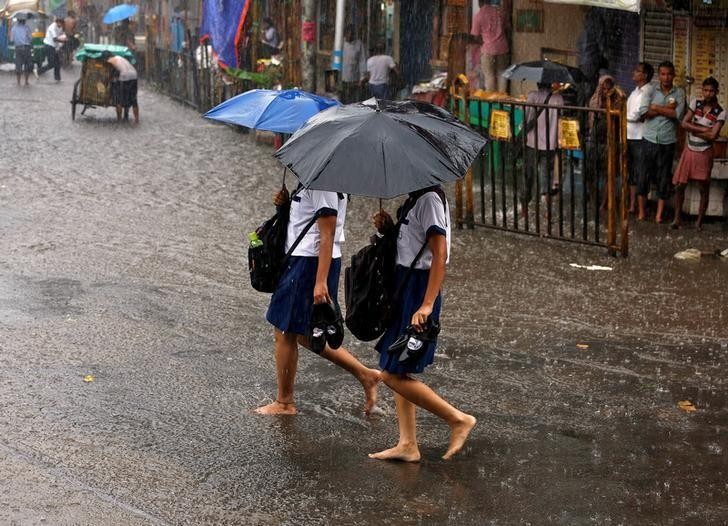 School girls walk barefoot as they cross a waterlogged road during rains in Kolkata, July 25, 2016. REUTERS/Rupak De Chowdhuri/Files