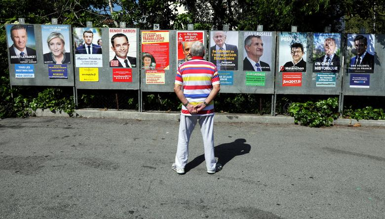 FILE PHOTO: A man looks at campaign posters of the 11th candidates who run in the 2017 French presidential election in Saint Andre de La Roche, near Nice, France, April 10, 2017. L-R : Nicolas Dupont-Aignan, Debout La France group candidate, Marine Le Pen, French National Front (FN) political party leader, Emmanuel Macron, head of the political movement En Marche ! (Onwards !), French Socialist party candidate Benoit Hamon, Nathalie Arthaud, France's extreme-left Lutte Ouvriere political party (LO) leader, Philippe Poutou, Anti-Capitalist Party (NPA) presidential candidate, Jacques Cheminade, ''Solidarite et Progres'' (Solidarity and Progress) party candidate, lawmaker and independent candidate  Jean Lassalle, Jean-Luc Melenchon, candidate of the French far-left Parti de Gauche, Francois Asselineau, UPR candidate, and Francois Fillon, the Republicans political party candidate.  REUTERS/Eric Gaillard/File Photo