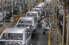 Des employés travaillent sur des voitures au sein d'une usine automobile Peugeot Citroën dans le complexe industriel chinois de Dongfeng. PSA a besoin d'accélérer ses réductions de coûts en Chine, a déclaré mardi le président du directoire du constructeur automobile au salon de Shanghai. /Photo d'archives/REUTERS