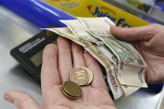 Продавец магазина в Красноярске пересчитывает деньги. Реальная заработная плата в РФ в марте 2017 года, по оценке Росстата, выросла на 1,5 процента в годовом выражении и на 4,9 процента к предыдущему месяцу.      REUTERS/Ilya Naymushin
