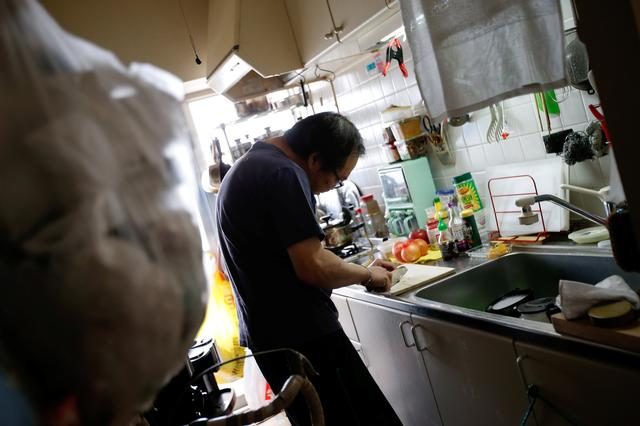 Akihiro Karube, 53, who lives with his widowed 84-year-old dad, cooks in a kitchen at his public housing in Hino, suburb of Tokyo, Japan, February 23, 2017. REUTERS/Toru Hanai