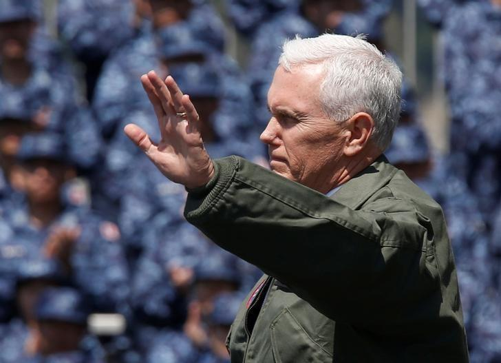 U.S. Vice President Mike Pence waves to U.S. and Japanese service members on the flight deck of the USS Ronald Reagan, a Nimitz-class nuclear-powered super carrier, at the U.S. naval base in Yokosuka, south of Tokyo, Japan April 19, 2017. REUTERS/Kim Kyung-Hoon