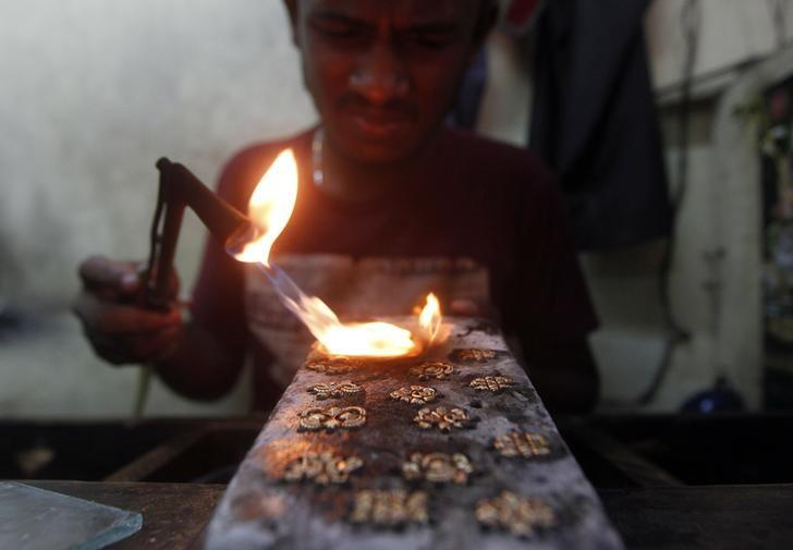 An employee makes gold studs at a jewellery workshop in Colombo December 2, 2013.  REUTERS/Dinuka Liyanawatte