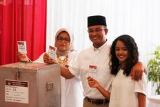 Candidate Anies Baswedan casts his vote along his wife Fery Farhati Ganis (L) and daughter Mutiara Annisa in the Jakarta governor election in South Jakarta, Indonesia April 19, 2017. REUTERS/Beawiharta