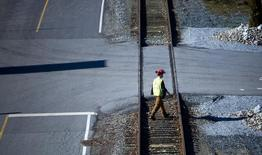 A railyard worker walks along the tracks at the Canadian Pacific railyard in Port Coquitlam, British Columbia February 15, 2015.   REUTERS/Ben Nelms