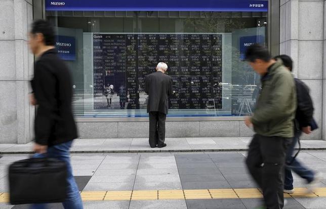 4月20日、寄り付きの東京株式市場で、日経平均株価は前営業日比14円19銭高の1万8446円39銭となり、小幅に4日続伸して始まった。写真は株価ボードを眺める男性、都内で昨年4月撮影(2017年 ロイター/Toru Hanai)