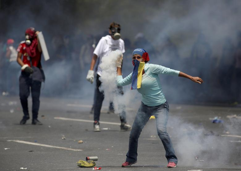 "Demonstrators clash with riot police during the so-called ""mother of all marches"" against Venezuela's President Nicolas Maduro in Caracas. REUTERS/Marco Bello"