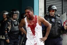 Un manifestante herido se ubica cerca de la policía durante unas protestas contra el presidente Nicolás Maduro en San Cristóbal, Venezuela, 19 de abril del 2017. Tres personas murieron por disparos el miércoles en Venezuela, dos de ellos estudiantes universitarios, durante una masiva jornada de protestas contra el Gobierno de Nicolás Maduro, lo que lleva a ocho los fallecidos en las últimas manifestaciones. REUTERS/Carlos Eduardo Ramírez