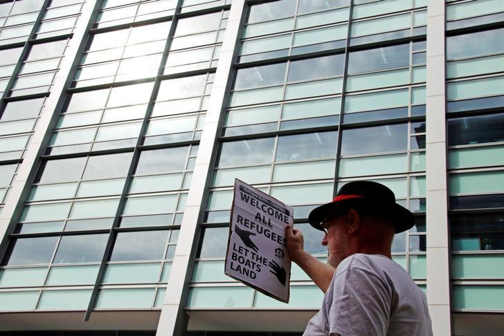 A protester from the Refugee Action Coalition holds a placard during a demonstration outside the offices of the Australian Government Department of Immigration and Border Protection in Sydney, Australia, April 29, 2016.   REUTERS/David Gray