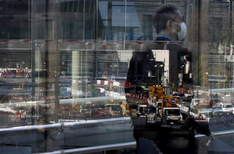 A construction site is reflected on a window as a businessman walks in Tokyo's business district, Japan January 20, 2016. REUTERS/Toru Hanai