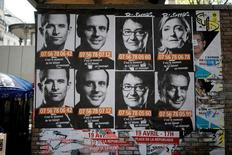 Предвыборный постер с портретами кандидатов в президенты Франции на стене в Париже 19 апреля 2017 года. Вероятное закрытие позиций инвесторами в четверг, когда до первого тура президентских выборов во Франции осталось менее 24 часов торгов, привело к ралли евро, росту акций французских банков и сокращению спредов доходности госбондов. REUTERS/Benoit Tessier