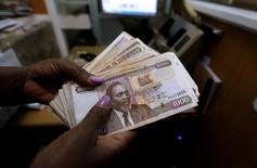 A teller counts Kenya shilling notes inside the cashier's booth at a forex exchange bureau in Kenya's capital Nairobi, April 20, 2016. REUTERS/Thomas Mukoya/File Photo